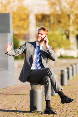 businessman makes a rest in the city, sits on a post and takes a phone call