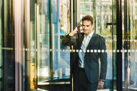 businessman with earphones comes out of a revolving door of an office building
