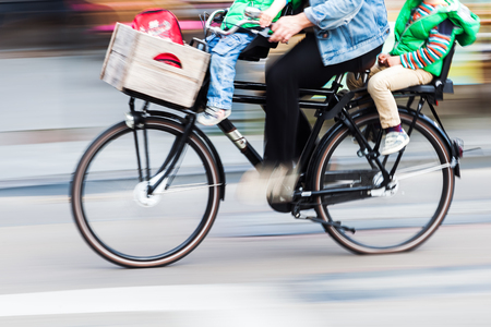 picture in motion blur of a cyclist with two children on the bicycle on a city street