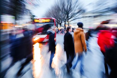 카메라로 사진을 황혼에 도시 거리를 건너는 사람들의 줌 효과를 만들었 스톡 콘텐츠