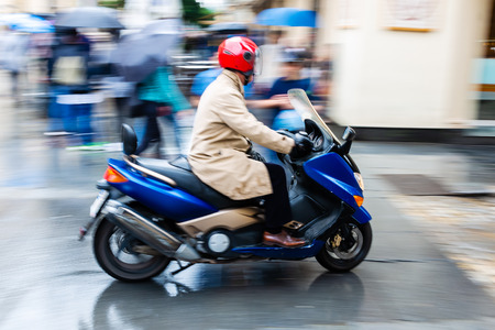 picture of a scooter in motion blur on a wet city street