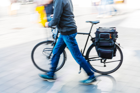 picture with motion blur effect of a man pushing his bicycle in the city