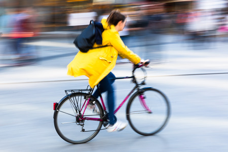 picture of a person riding a bicycle in a city in motion blur