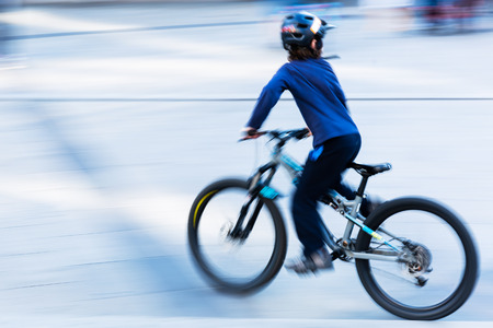 motion blur picture of a young boy who rides a bicycle