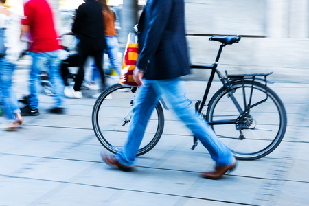 Businessman pushing a bicycle in the city in motion blur