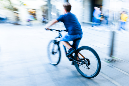young person rides a bicycle at the city in motion blur