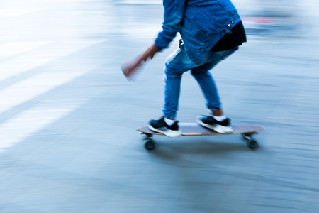Young person with a skateboard in motion blur