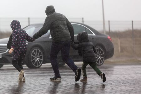 picture of a family who is crossing a street while it is heavy raining
