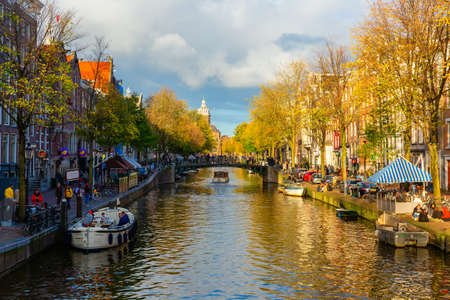 Amsterdam, Netherlands - October 28, 2020: cityscape with typical canal in Amsterdam, with unidentified people. Amsterdam is the capital and most populous city in the Netherlands