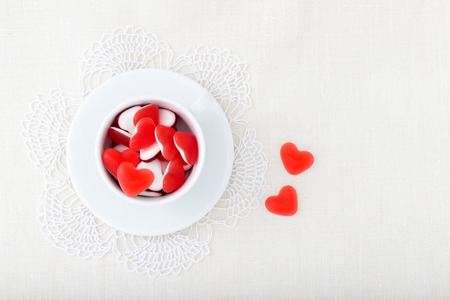 Close up image of red heart jelly in the white coffee cup photo