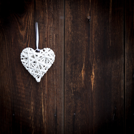 White wicker heart on wooden background photo