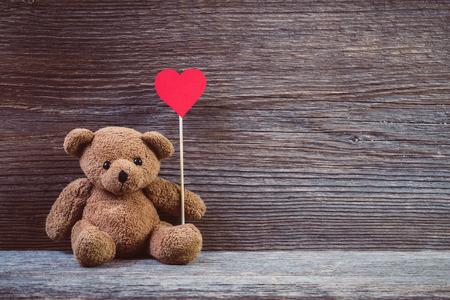Teddybeer met hart zit op oude houten achtergrond.
