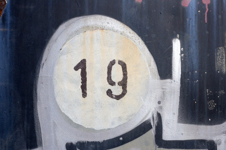 19: Number 19 on old painted and rusted metal panel