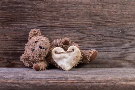 Teddy bear with heart sitting on old wood background. Stock Photo