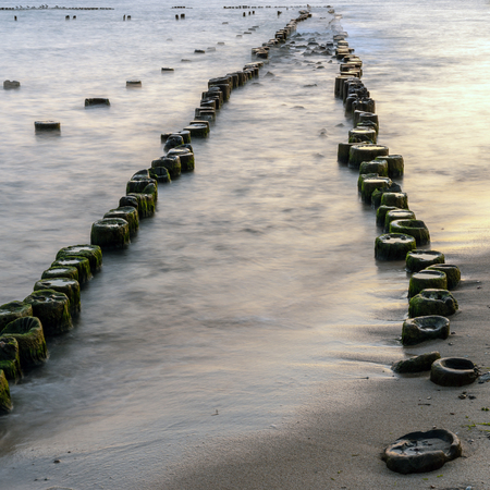 Wooden breakwaters on the sea shore. Stock Photo