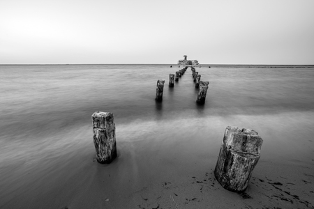 Wooden breakwaters on the sea shore. Фото со стока