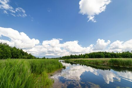 The blue sky with the clouds above the clear blue river