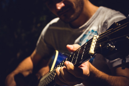 Guitar player singing in a park sitting on a tree Stock Photo