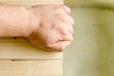 Close up shot to a hand holding to a wooden floor next to water