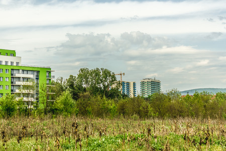 conquers: Landscape shot to a few buildings in meadow where the civilization conquers the nature on a cloudy day