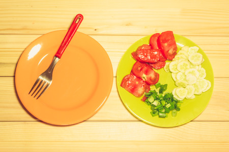 A few sliced vegetables on a plate next to an empty orange platewith a fork on it on a wooden background Reklamní fotografie