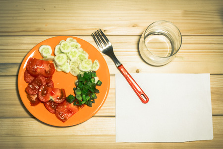 A few sliced vegetables on a plate next to an empty glass, a fork and a white plain piece of paper on a wooden background