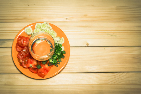 A few sliced vegetables on a plate with an empty glass on top of them on a wooden background