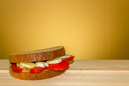 Shot to a vegetarian sandwich made from a few slices of tomato and a few slices of cucumber on a wooden table