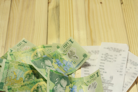 leu: A few romanian LEU next to some grocery receipts on a wooden table Stock Photo