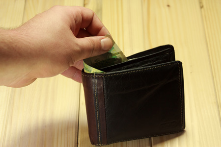 leu: Shot of a hand taking some romanian money out from a wallet standing on a wooden table