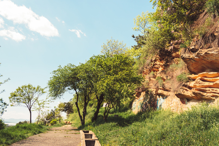 A path with trees and grass near a rocky wall somewhere in Romania