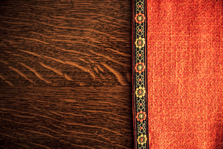 wood texture: Shot to a rustic backround made from an orange rustic cloth and a dark brown wooden plank in Transilvania Stock Photo
