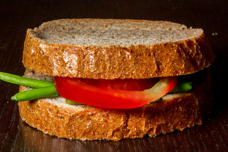 Close up shot to a simple sandwich made from a few green onion leafs and a slice of tomato on a wooden background