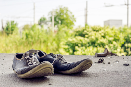 tearing down: Close up shot to a parir of used shoes that looks like they were lost Stock Photo