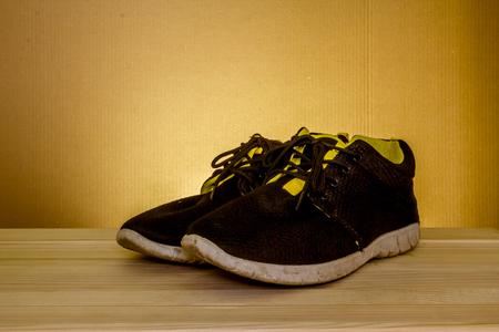 second floor: Elegant shot of  some used sport shoes sitting on a wooden table with a dark background Stock Photo