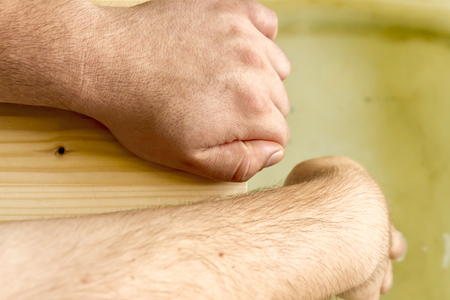 Close up shot to two hands holding to a wooden floor while one is testing the water Stock Photo