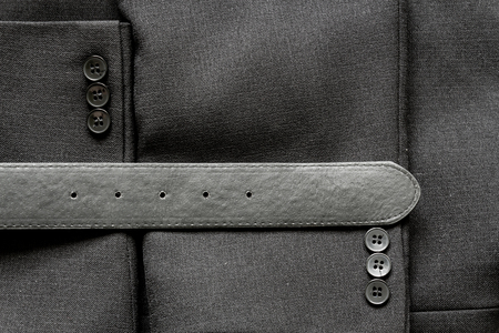 black leather texture: Close up of a few buttons on a business suit coat and a leather belt