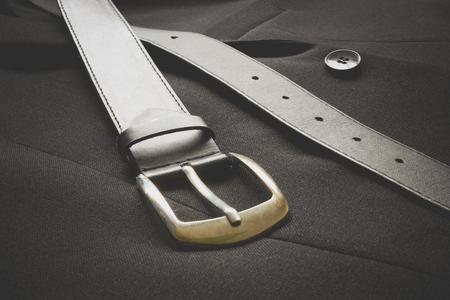 metalic: Closeup of a leather belt with metalic buckle near a suit button on a business coat Stock Photo