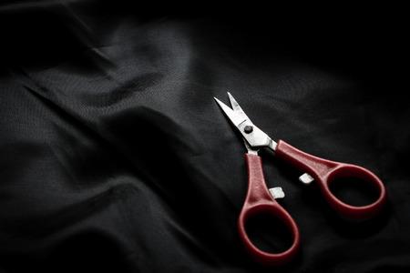 Small scissors on dark crumpled silk background