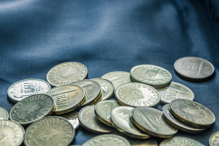 Mixed stack of european coins on a blue silk background