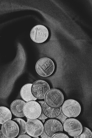 Mixed stack of european coins on silk background. Black and white picture Stock Photo