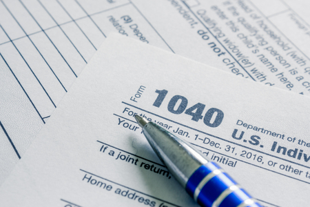 Tax form business financial concept: macro view of individual return tax form and blue open pen