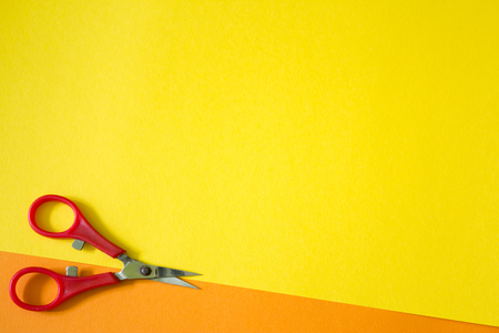 red scissors on orange and yellow background