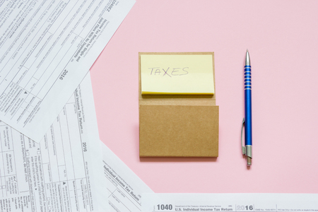 US tax form 1040 with note and pen. tax form. law document usa. pink background. mathematics business concept. Stock Photo