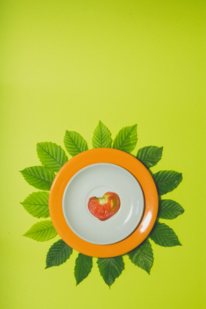 Minimal hearth shaped tomato slice background. Fruit on white and orange colored plate with leaves around it. Vertical cover, banner, flyer, leaflet, page design