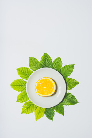 Minimal orange slice background. Fruit on white plate with leaves around it. Matte colored. Vertical design for a leaflet, banner, cover or flyer Stock Photo