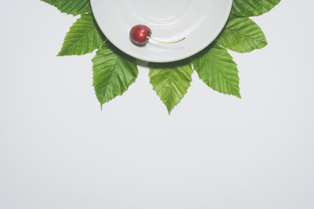 Minimal cherry background. Fruit on white plate with leaves around it. Matte colored.