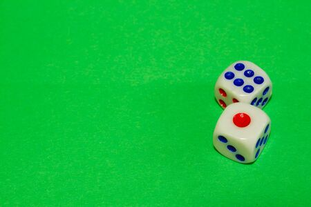 Two white dices with red and blue dots on green table. Casino gambling concept image Stock Photo