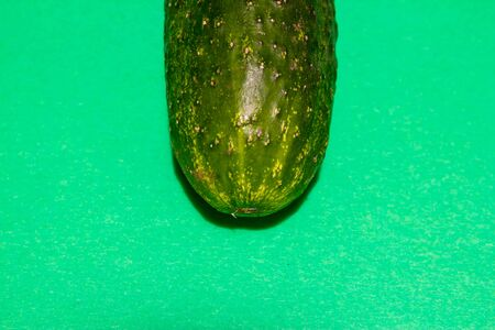 Closeup of a cucumber top positioned on the top o f the shot on a green background