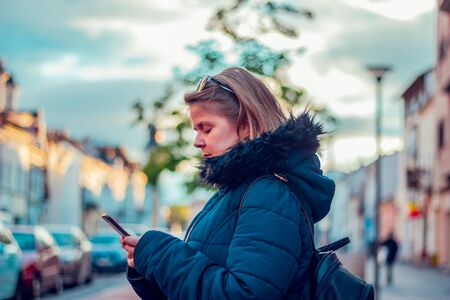 Young woman with brown hair wearing a hooded thick jacket and sunglasses on her head holding a black phone on a cold day – Girl using mobile phone for texting and communication